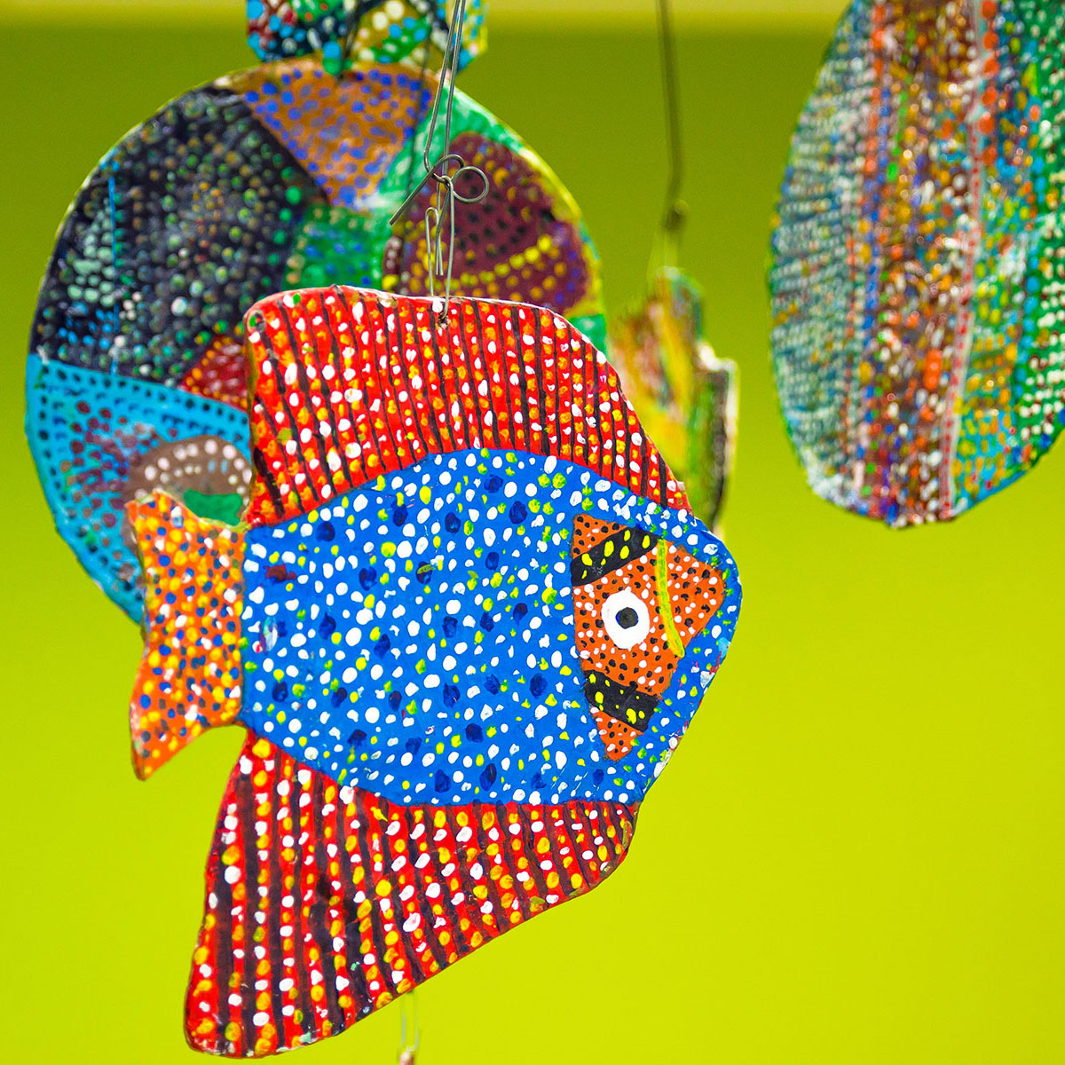 A photo of some brightly coloured artwork hanging from a ceiling